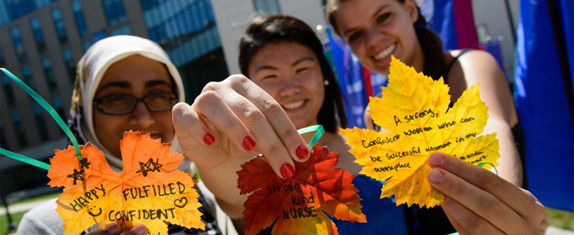 Students holding autumn leaves with words of inspiration written on them.